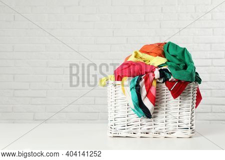 Wicker Basket With Laundry On Table Near White Brick Wall. Space For Text