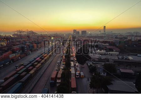 Evening Traffic Jam At City Industrial Area. Cargo Container Warehouse At Sea Port And Sunset City P