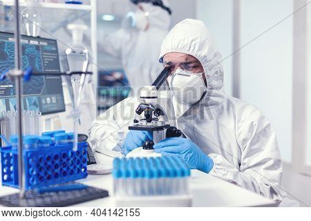 Lab Technician In Ppe Gear Examining Virus Samples Under Microscope In Laboratory. Scientist In Prot