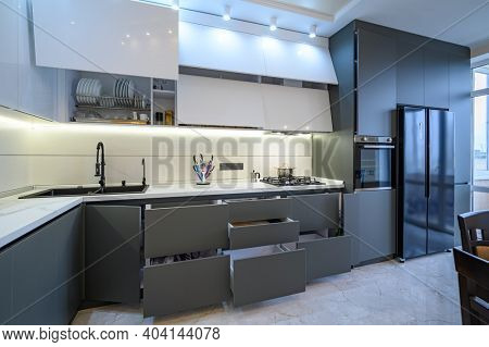 Spacious luxury white and dark grey modern kitchen interior with dining table, most furniture drawers and doors are open