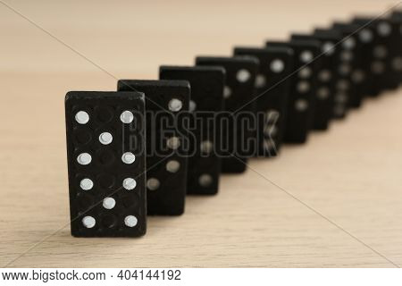 Black Domino Tiles With White Pips On Wooden Table, Closeup