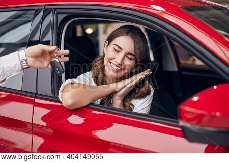 Delighted Young Female Driver Smiling With Closed Eyes And Clasping Hands While Sitting In Red Vehic