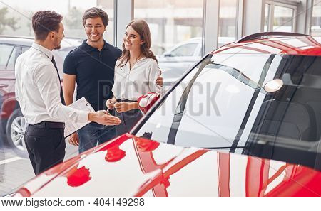 Modern Young Woman And Man Chatting With Dealer While Picking New Red Car In Salon