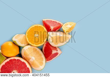 Top View Of Halves Of Citrus Fruits. Citrus Pattern On Blue Background. Flatlay. Fresh Cool Summer L