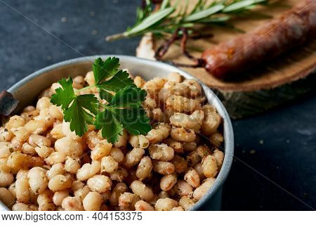 botifarra amb mongetes, sausage and fried white beans, a traditional dish of catalonia, spain, served in an old metallic lunch box