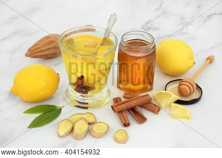 Immune boosting health food for cold and food remedy with hot drink of honey, lemon, ginger and cinnamon spice on marble. Very high in antioxidants and vitamin c.