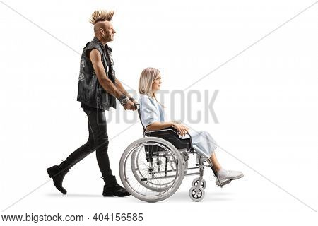 Punk man pushing a young woman patient in a wheelchair isolated on white background