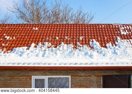 Metal Roof In The Snow In Winter. Descent Of Snow Avalanches From Rooftops.