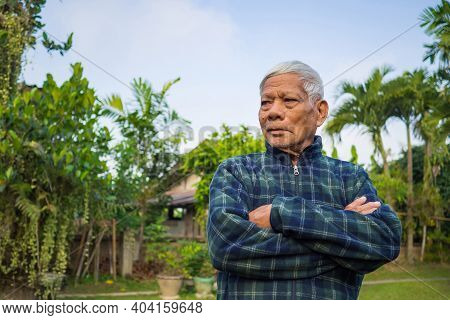 Portrait Of Elderly Man Arms Crossed And Looking Away While Standing In A Garden. Space For Text. Co