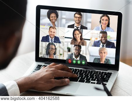 Black Businessman Having Online Business Meeting With Colleagues Making Video Call On Laptop Sitting