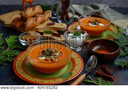 Tomato Puree Soup With Baked Peppers On Beautiful Bright Plates With Croutons And Sour Cream Sauce.