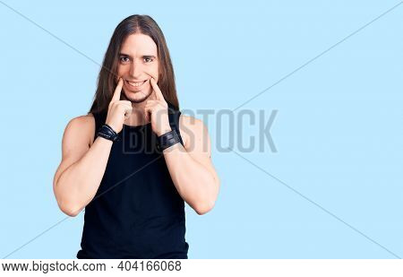 Young adult man with long hair wearing goth style with black clothes smiling with open mouth, fingers pointing and forcing cheerful smile