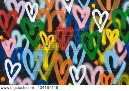 Abstract Background With Multicolored Hearts Painted With Paint. The Wall Is Brightly Painted With A