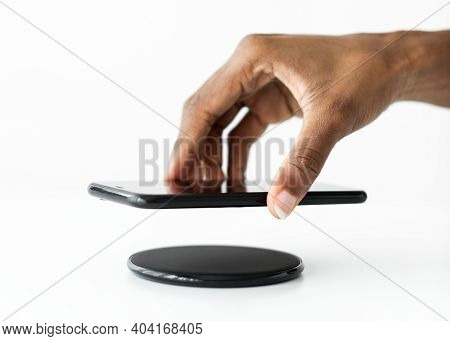 Hand connecting smartphone to wireless charger