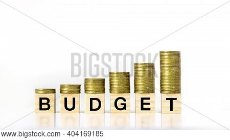 A Growing Stack Of Coin Steps On A Wooden Block Labeled Budget On A White Background, Investment Bud