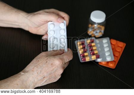 Elderly Woman With Pills In Wrinkled Hands. Different Medication In Tablets And Capsules, Taking Sed