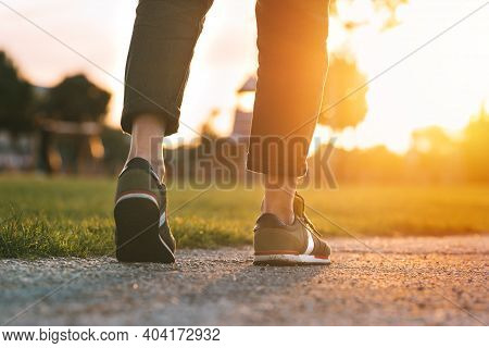 Woman Walking In The Park At Sunset. Closeup On Shoe With Rolled Up Jeans. Taking A Step. Woman On H