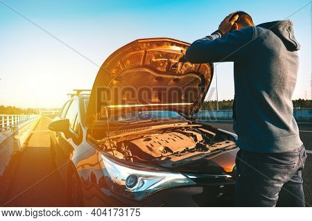 Stressed Man Having Trouble With His Broken Car On The Highway Roadside At Sunset. Man Looking Under