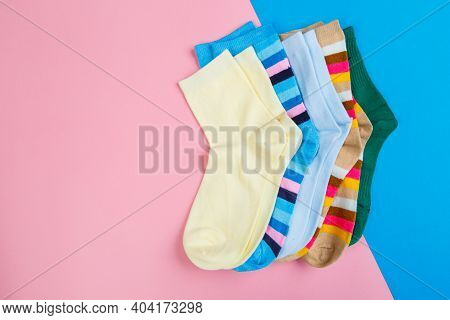 Multicolored Jersey Socks On A Pastel Pink And Blue Background. View From Above