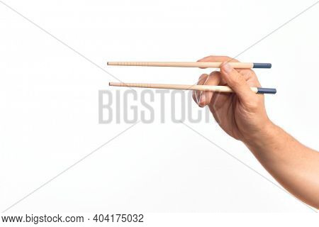 Hand of caucasian young man holding chopsticks over isolated white background