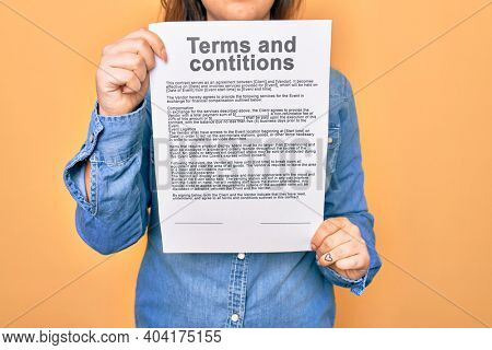 Woman holding terms and conditions document paper standing over isolated yellow background