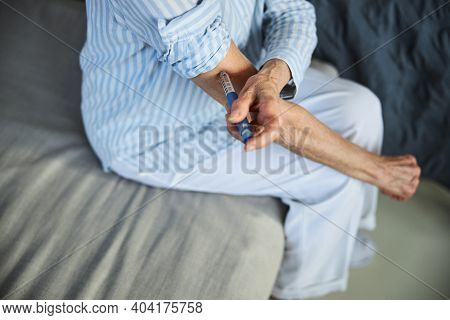 Senior Adult Putting A Syringe Needle In Her Hand