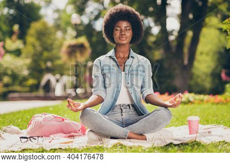 Photo Portrait Of Black Skinned Young Woman Sitting In City Green Park Near Bag Doing Yoga Asana Lot