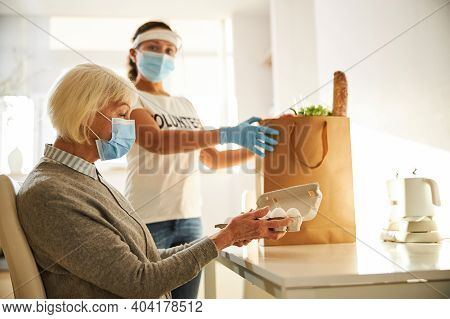 Caregiver Supplying Provisions For A Senior Lady