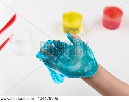 Toy Slime In The Hand Of A Child On A Light Background. The Child Plays With Mucus And Develops Fine