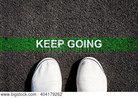 Keep Going. The Inscription On The Green Line On The Asphalt. Sneakers. View From Above. Copy Space.