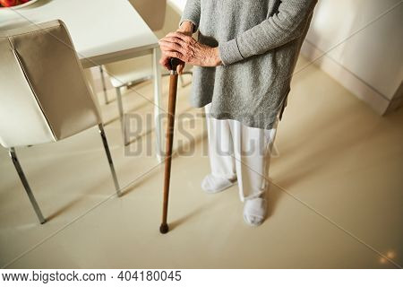 Woman In Pants And A Tunic Using A Cane