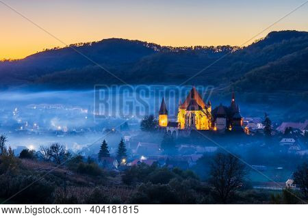 Biertan, Romania. Foggy Sunset At The Saxon Village With The Fortified Church, Transylvania.