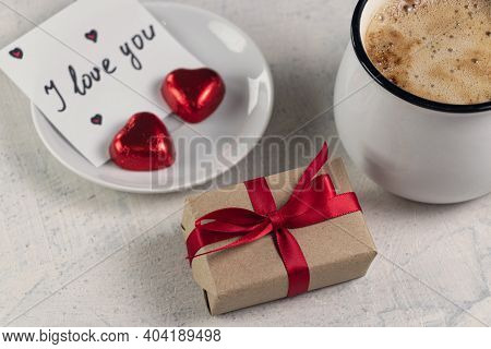 A Gift With A Red Ribbon, A Mug Of Coffee, Heart-shaped Chocolates And A Note With The Word I Love Y