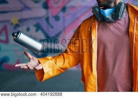 Graffiti Artist Throw His Spray Paint Can Against Colorful Graffiti On Wall. Street Art And Contempo