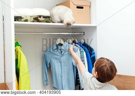 Boy Standing By Wardrobe With Clothes. Cute Boy Taking School Shirt To Wear.