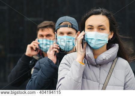 Group Of Young Volunteers Wearing Face Masks With Mobile Phones. Volunteers Are Ready To Help. Call