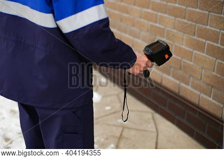 Close-up Shot Of Man Hand Recording Heat Loss With Infrared Thermal Camera Outside Home. Recognition
