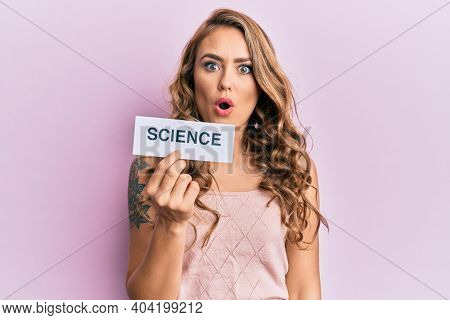Young blonde girl holding paper with science message scared and amazed with open mouth for surprise, disbelief face
