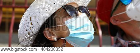 A Man And A Woman In Medical Masks And Sunglasses Look Up. Young People Protect Themselves From The