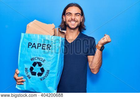 Young handsome man holding recycling wastebasket with paper and cardboard screaming proud, celebrating victory and success very excited with raised arm
