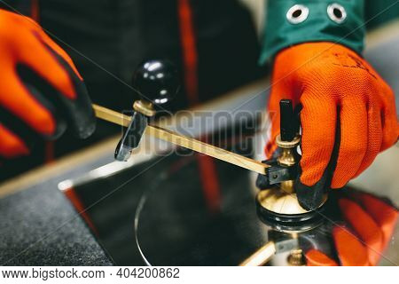 Glazier worker cutting glass with compass glass cutter in a workshop. Industry