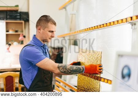 Glazier worker preparing glass in workshop. Industry and manufactory production
