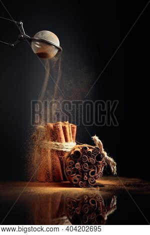 Cinnamon Powder Is Poured Out Of The Strainer. The Ground Cinnamon, Cinnamon Sticks, Tied With Jute