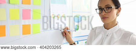 A Woman In Business Clothes Is Standing By A White Board With Stickers. An Employee Stands In The Of