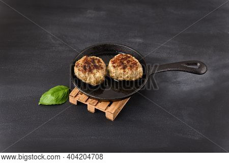 Fried Meatball In A Frying Pan On A Woodenpalet Trivet, With Basil Leaves.