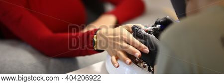 The Woman Holds Out Her Hand To The Manicure Master. The Master Performs The Stages Of Coating The N