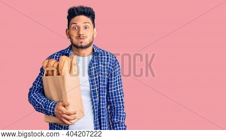 Handsome latin american young man holding paper bag with bread puffing cheeks with funny face. mouth inflated with air, crazy expression.