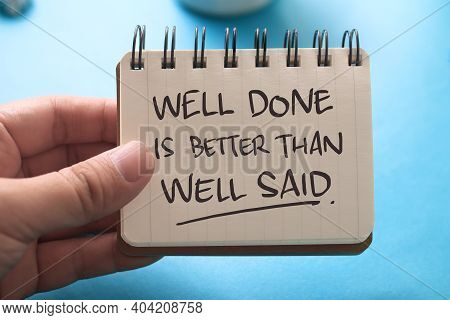 Well Done Is Better Than Well Said, Text Words Typography Written On Book Against Blue Background, L