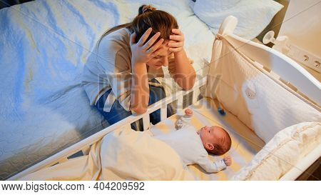 Young Tired Mother Suffering From Depression Lookin On Her Sleepless Newborn Baby In Crib At Night.