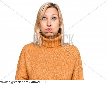 Middle age caucasian woman wearing casual winter sweater puffing cheeks with funny face. mouth inflated with air, crazy expression.
